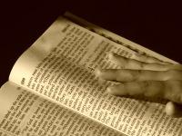 hand touching the Bible